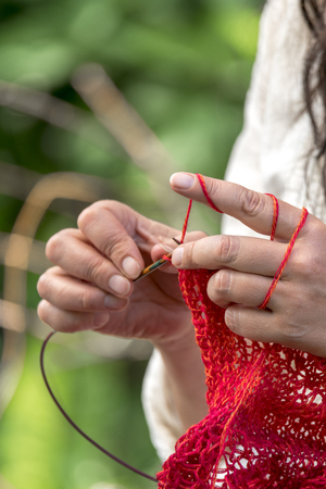 Hands of a woman wearing crochet with red wool / knits in front of a blurred background