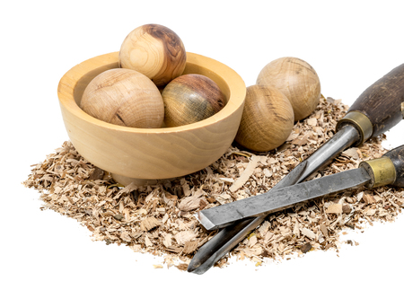 Hand-turned wooden balls in a bowl decorated with sawdust and tool isolated on white