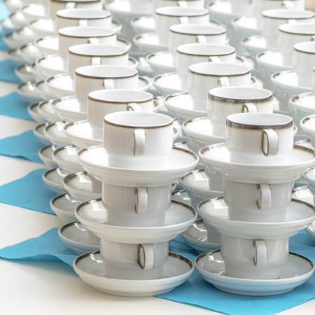 White coffee cups with plates stand stacked in a row Stock Photo
