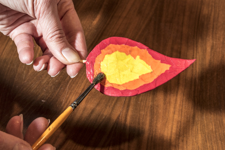 Christmas crafts - painting a handmade candle flame for a decoration Stock Photo