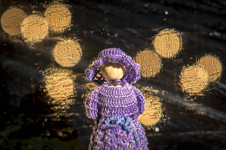 Wooden doll with crocheted blue dress against blurred background with bright lights Standard-Bild - 116295319