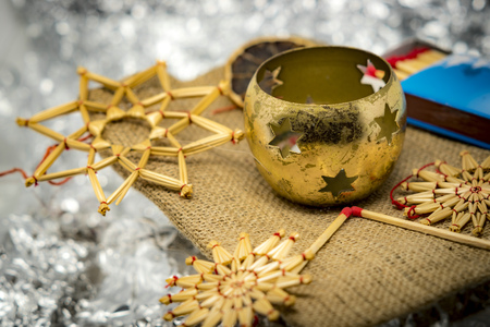 Golden Christmas decoration with straw stars, candlesticks and matches with shiny silver background Standard-Bild - 116295320