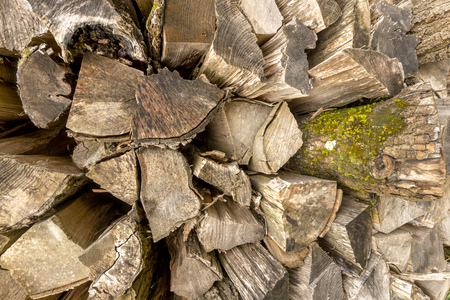 Old split weathered tree trunks stacked as firewood. Standard-Bild - 116295385