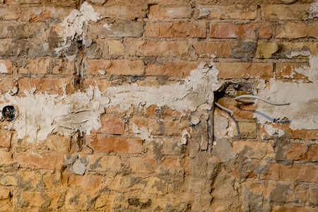 Brick wall with holes for power sockets and cables during a renovation as a background Standard-Bild - 116295573