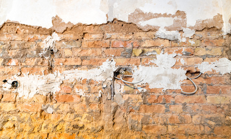 Brick wall with holes for power sockets and cables during a renovation as a background Standard-Bild - 116295574