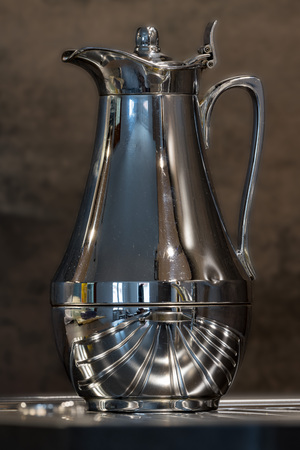Shiny used coffee pot with strong reflections against a dark background Banco de Imagens