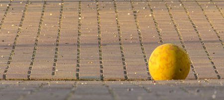 Yellow Kids Ball Lies on a Paved Place in front of Blurred Background