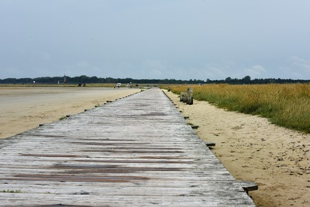 Wooden pier on the German North Sea coast on the sandy beach with dike and lighthouse