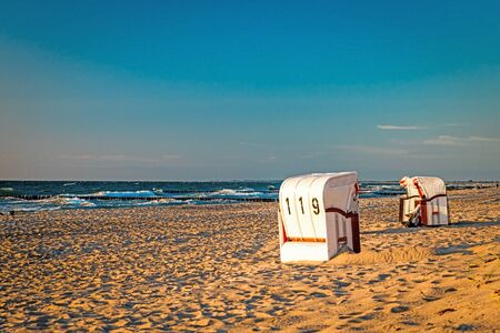 Beach chairs stand in the sunset on a beach on the Baltic Sea with sea and clear sky Фото со стока