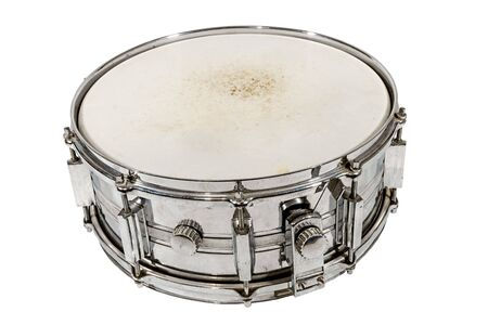 Old silver Snare drum stands on the ground isolated on white