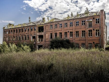 Industrial building covered with shrubs. Ruin with sunken roof against cloudy blue sky Фото со стока