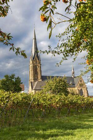 Catholic Church Edenkoben Germany Rhineland Palatinate with fountain and cloudy blue sky Фото со стока