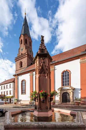 Protestant Church Edenkoben Germany Rhineland Palatinate with fountain and cloudy blue sky