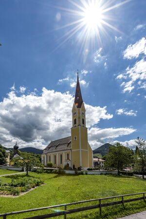 Church at Schliersee in Bavaria Germany with sun and blue cloudy sky