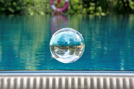 Glass ball hovers over a swimming pool with mirrored cloudy sky and trees Stock Photo