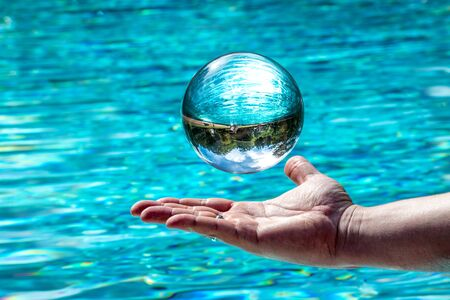 Glass ball hovers over a hand in front of water. Background with mirrored cloudy sky and trees
