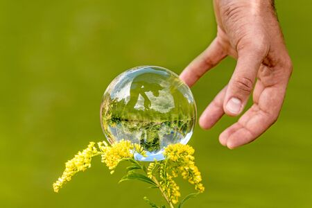 A man's hand reaches for a glass globe with a mirrored lake, trees and cloudy sky against a green background