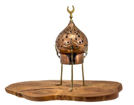 Old oriental incense burner made of copper stands on a wooden disc