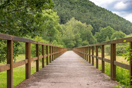 Bridge made of wooden boards over a green field with trees and wooded hills