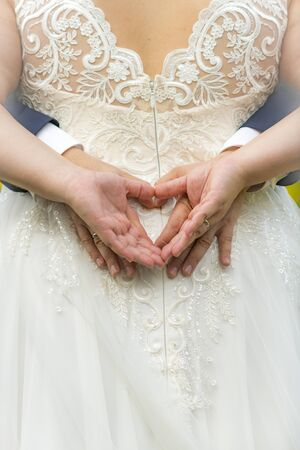 Four hands form a heart on the back of a white wedding dress