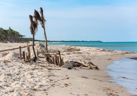 German Baltic Sea coast with sand dunes, grass, water and blue sky with Wood sign