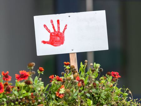 Shield with painted red hand stands in a flowerbed with copy space