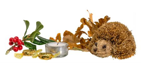 Christmas decoration with autumn leaves, candle and straw hedgehog in front of white background