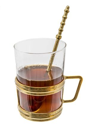 Glass with metal handle and spoon of bronze filled with hot tea isolated on white