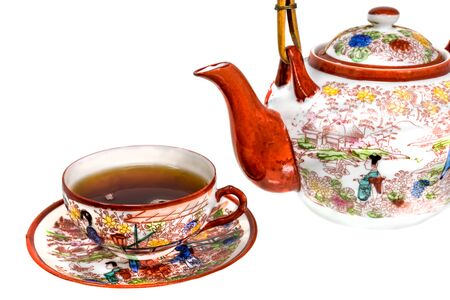 Tea cup filled with tea and teapot of painted Chinese porcelain isolated on white Stock Photo