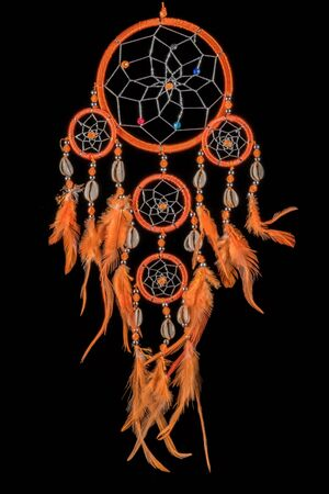 Pearl-embroidered dream catcher with colorful feathers and pearls against a black background 写真素材