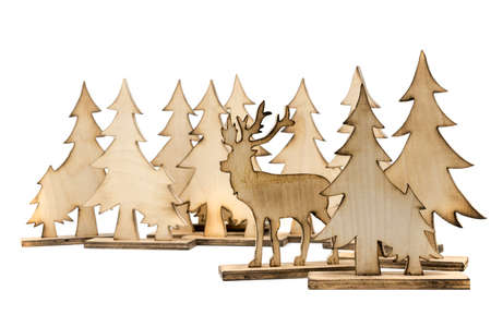 Cut out deer figure made of wood with dark edges and wooden fir trees