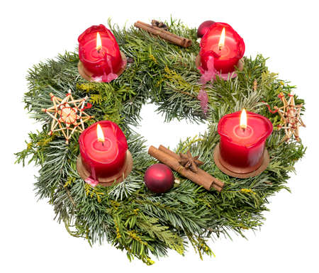 Top view of a decorated Christmas wreath made of fir branches with burning red candles