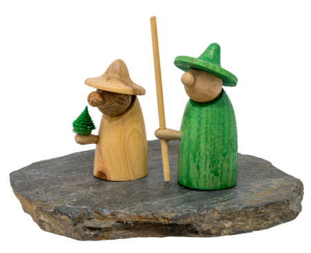 Two wooden christmas figure stand on a dark wooden board