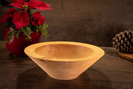 A turned rustic light wooden bowl stands on a dark surface with flowers in the background