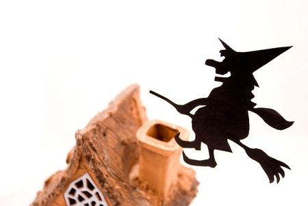 Witch,flying on broom on house,on white background photo