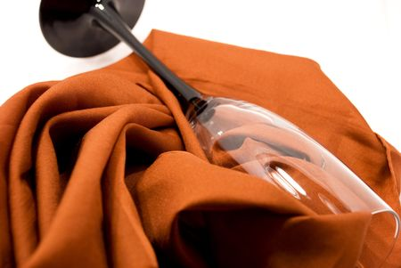 pleat: Tall wine glass lying on table, on fabrics in pleat,on white background