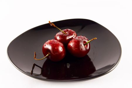 cherries on a plate on a white background photo