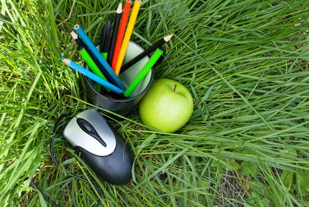 computer mouse, apple and pencils in a glass, on the grass photo