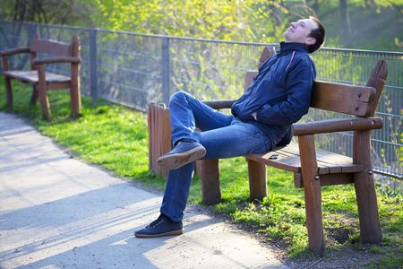 a man sitting on a park bench photo