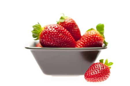 juicy strawberries in a bowl isolated on white photo