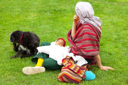woman sitting on the grass with a child and a dog photo