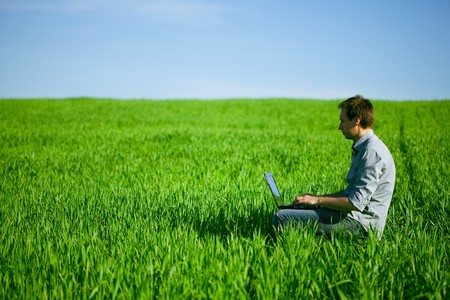 horizonte: Hombre joven utilizando un ordenador port�til al aire libre  Foto de archivo