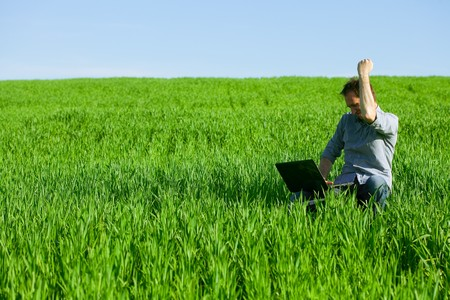Young man using a laptop outdoors photo