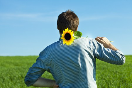 young man standing with a sunflower in the green field photo