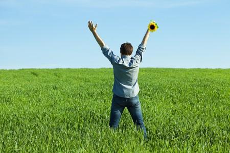 giovane uomo in piedi con un girasole nel campo verde