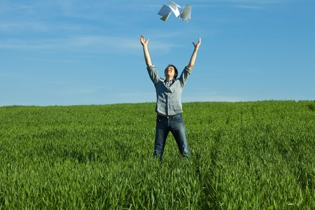 young man throwing a paper in the green field Stock Photo - 7200543