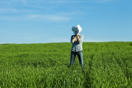 young man covering the face paper in green field Stock Photo - 7200671