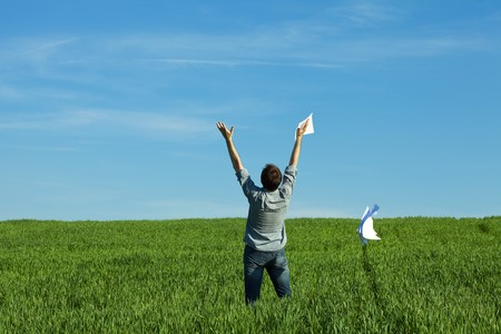 young man throwing a paper in the green field Stock Photo - 7200340