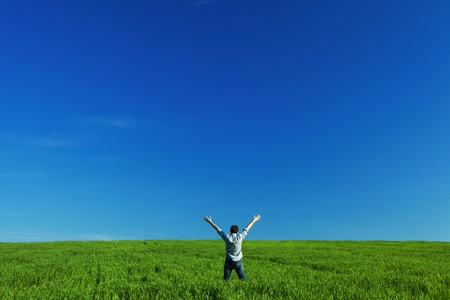 young man outstretched arms in green field against the blue sky Stock Photo