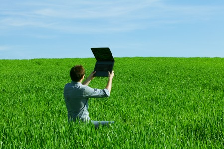 young man using laptop in the field photo